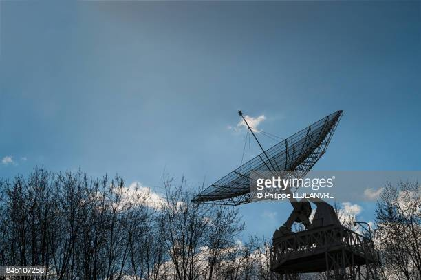 Astronomic parabolic radio antenna in woods against blue sky