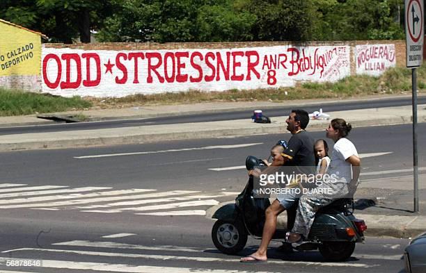 Una familia en motocicleta aguarda para cruzar el 18 de febrero de 2006 en Asuncion frente a un cartel del empresario Osvaldo Dominguez Dibb nieto...
