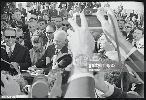 Soviet President Nikolai Podgorny and Egyptian President Anwar Sadat are surrounded by a crowd of dignitaries and newsmen as they cut the ceremonial...