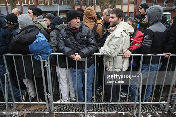 Asylum applicants wait outside the the Central Registration Office for Asylum Seekers of the State Office for Health and Social Services to receive...