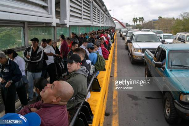 Asylum seekers and Mexican citizens wait on the international bridge from Mexico to the United States on December 09 2019 next to the border town of...