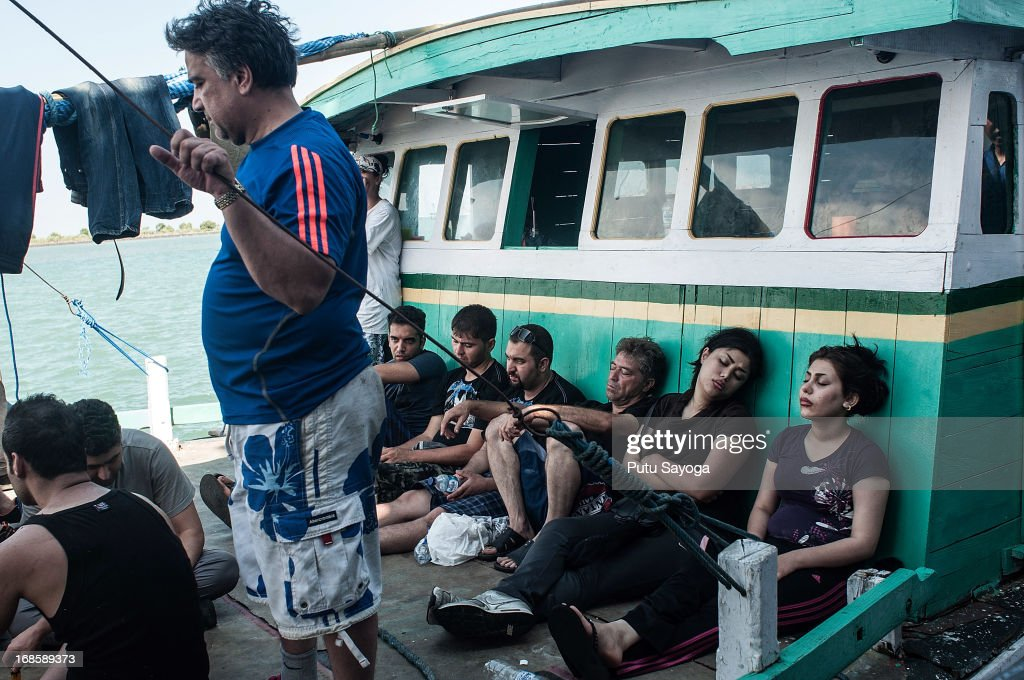 Asylum seekers are seen resting on a boat on May 12, 2013 in Bali, Indonesia. Indonesian police have intercepted an asylum seeker boat harboured in Bali that was believed to be heading to Australia. 80 to 100 people of Middle Eastern origin where found in the hull of a wooden boat on Benoa Harbour.