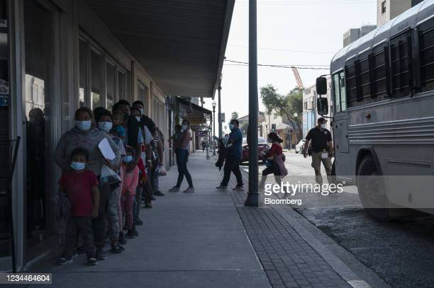 Asylum seekers arrive at a COVID-19 testing site after being processed by U.S. Immigration officials in McAllen, Texas, U.S., on Wednesday, Aug. 4,...