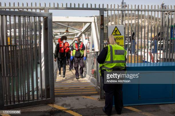 Asylum seekers arriving into Dover up the dock walkway ramp accompanied by Boarder Force officers after being on board a Boarder Force RIB boat, they...