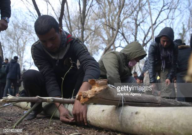 Asylum seekers build a ladder by tree branches to climb over the border fence as they continue to wait at the woodland between the Kastanies and the...