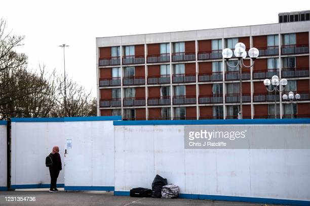Asylum seekers enter the Crowne Plaza hotel through an exterior perimeter wall that has been installed whilst they stay at the hotel on February 24,...