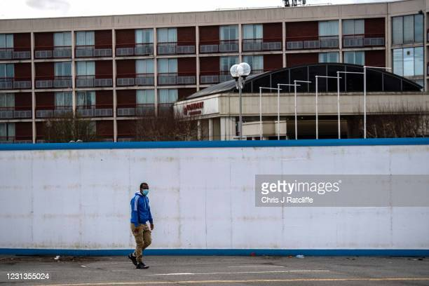 Asylum seekers exit the Crowne Plaza hotel through an exterior perimeter wall that has been installed whilst they stay at the hotel on February 24,...