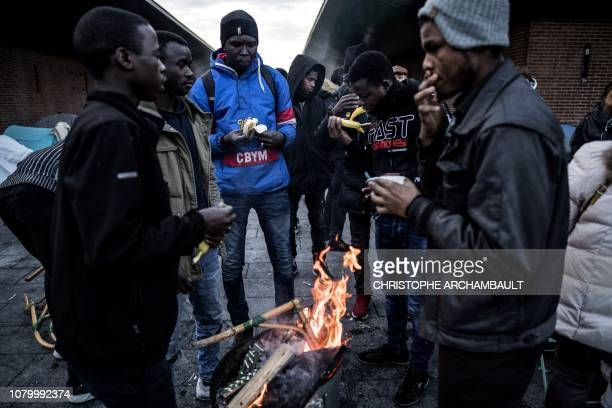 Asylum seekers from eastern African countries mainly Sudan warm themselves up around a brazier as they have a meal offered by volunteers of the...