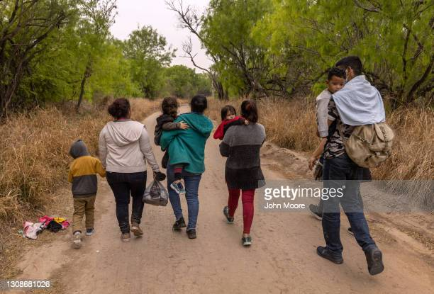 Asylum seekers from Honduras walk towards a U.S. Border Patrol checkpoint after crossing the Rio Grande from Mexico on March 23, 2021 near Mission,...
