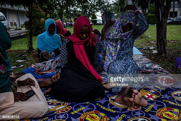 Asylum seekers from Sudan sit in the city park next to the regional parliament building for the city of Batam on September 5 2016 in Batam Indonesia...
