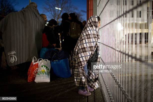 Asylum seekers from Syria stand at the fence of the State Office of Health and Social Affairs registration centre in Berlin on December 21 2015 / AFP...