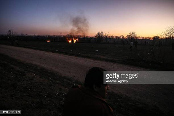 Asylum seekers gather around a fire to warm as they continue to wait in the region between the Kastanies and the Pazarkule border gates and Greek...