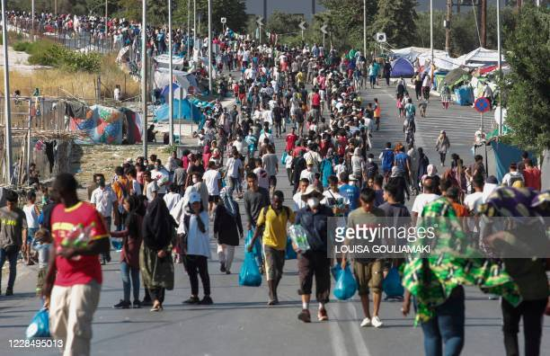 Asylum seekers gather as they wait for food distribution along the roadside where thousands are living with out shelter and exposed to the elements...