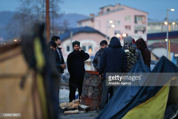 Asylum seekers get warm near fire as they wait to continue to move towards western European countries after tightened security measures at the border...