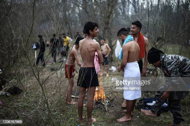 Asylum seekers have bath and wash their clothes at the Evros River as they continue to wait at woodland near buffer zone located between the...