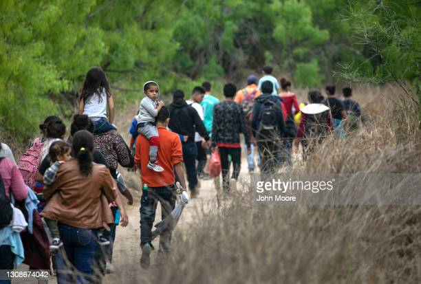 Asylum seekers, most from Honduras, walk towards a U.S. Border Patrol checkpoint after crossing the Rio Grande from Mexico on March 23, 2021 near...