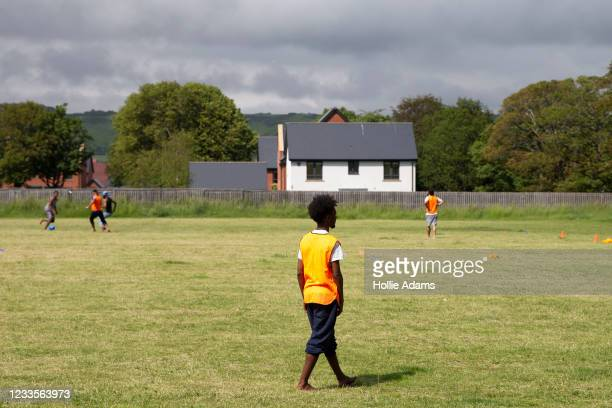 Asylum seekers play football during the Care4Calais event opposite the Napier Barracks on June 20, 2021 in Folkestone, England. A recent UK High...