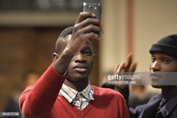 Asylum seekers pose for a selfie picture backstage before taking part in the special event 'Generation Africa' during the ITC Ethical Fashion...
