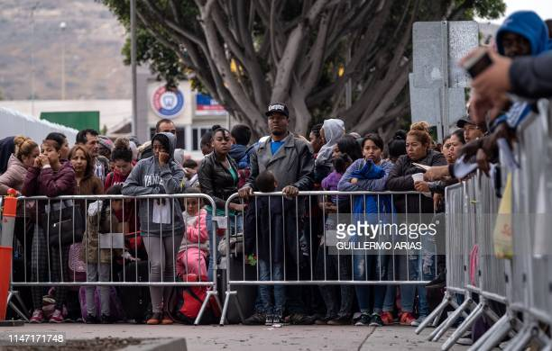 Asylum seekers queue for a turn for an asylum appointment with US authorities at the USMexico El Chaparral crossing port in Tijuana Baja California...