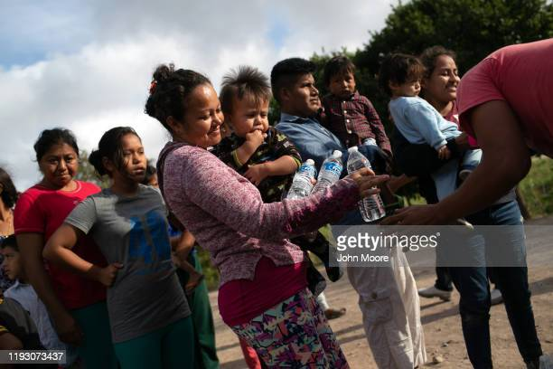 Asylum seekers receive bottled water at an immigrant camp on December 09, 2019 in Brownsville, Texas, across the river from the border town of...