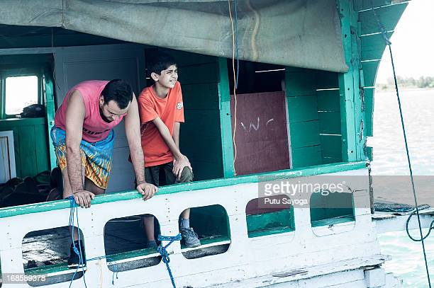 Asylum seekers sit on the back of a boat on May 12 2013 in Bali Indonesia Indonesian police have intercepted an asylum seeker boat harboured in Bali...