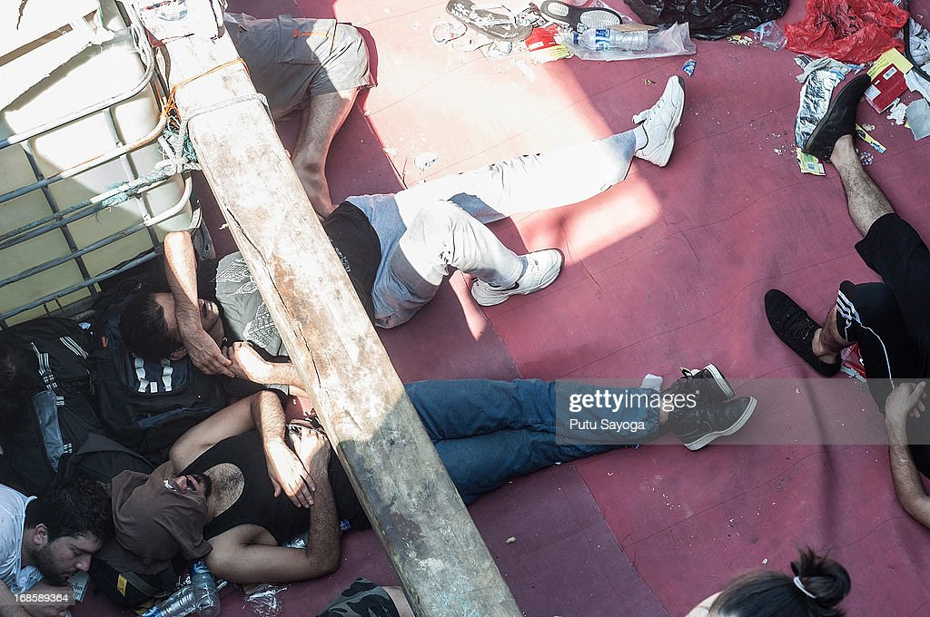 Asylum seekers sleep on a boat on May 12, 2013 in Bali, Indonesia. Indonesian police have intercepted an asylum seeker boat harboured in Bali that was believed to be heading to Australia. 80 to 100 people of Middle Eastern origin where found in the hull of a wooden boat on Benoa Harbour.