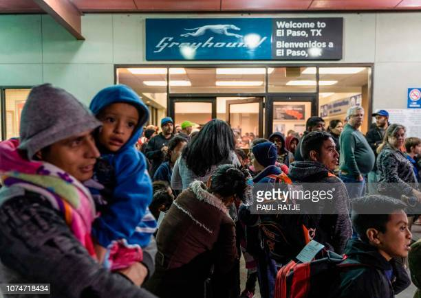 Asylum seekers stand at a bus stop after they were dropped off by Immigration and Customs Enforcement at the Greyhound bus station in downtown El...