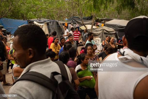 Asylum seekers stand for a headcount at a makeshift migrant camp in Matamoros Tamaulipas state Mexico on Friday March 20 2020 PresidentDonald...