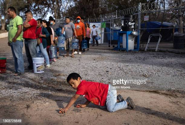 Asylum seekers stand in line to receive fresh water distributed at a migrant camp at the U.S.-Mexico border on February 23, 2021 in Matamoros,...