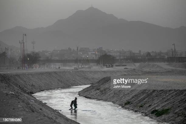 Asylum seekers wade through the Rio Grande while crossing from Mexico into the United States on March 16, 2021 from Ciudad Juarez, Mexico. An...