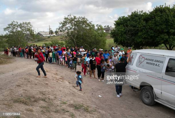 Asylum seekers wait for bottled water at an immigrant camp on December 09 2019 in Brownsville Texas across the river from the border town of...