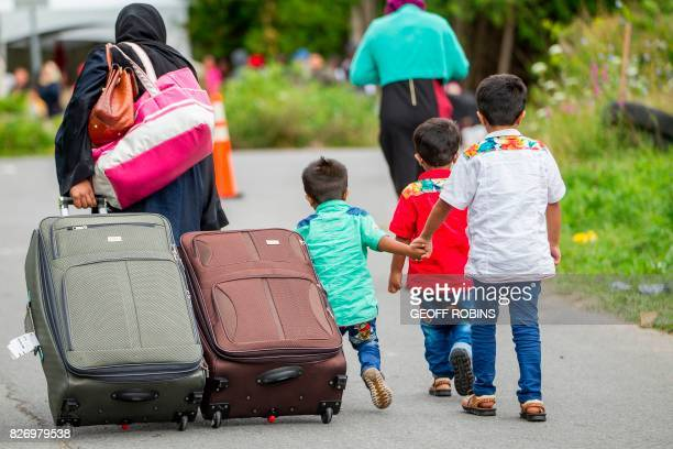 TOPSHOT Asylum seekers walk along Roxham Road near Champlain New York on August 6 making their way towards the Canada/US border In recent days the...