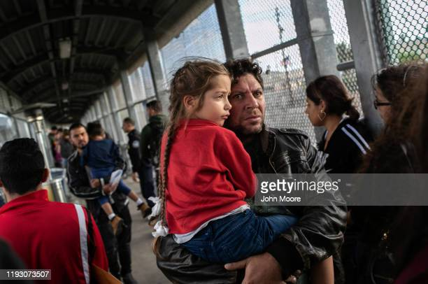 Asylum seekers walk back across the international bridge from the United States to Mexico after their immigration court hearing on December 09 2019...
