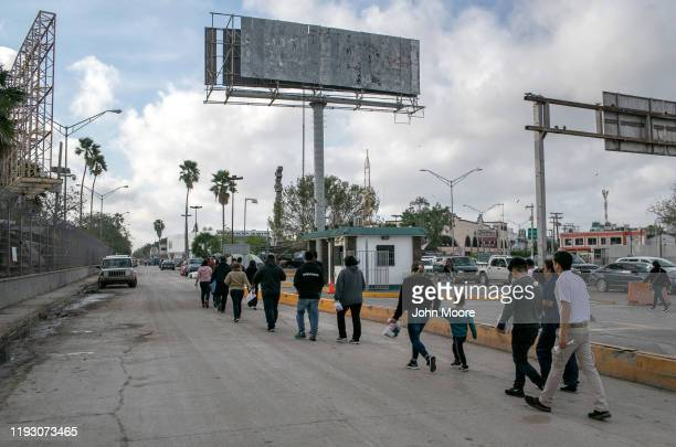Asylum seekers walk back into Mexico after their immigration court hearing on December 09, 2019 in Brownsville, Texas, across the river from the...