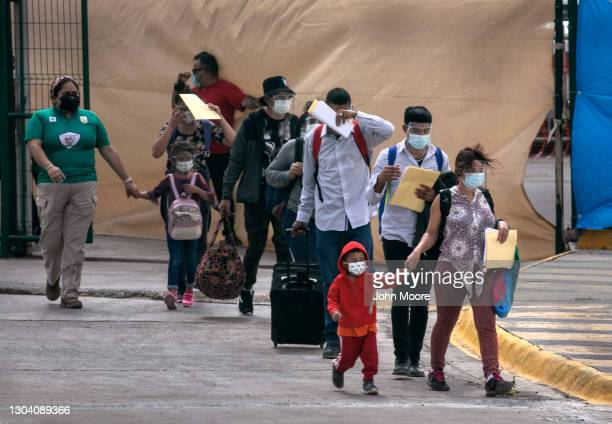 Asylum seekers walk to the U.S.-Mexico border as a group of at least 25 immigrants were allowed to travel from a migrant camp in Mexico into the...