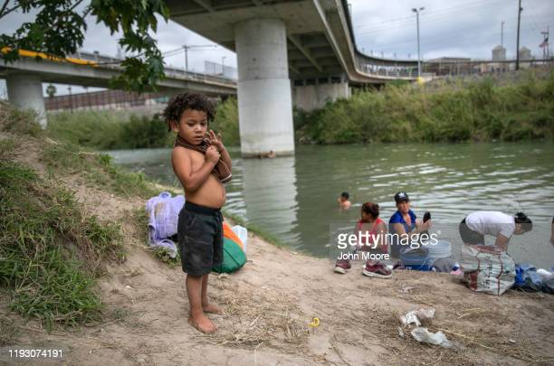 Asylum seekers wash clothes in the Rio Grande under the international bridge to the United States at an immigrant camp on December 08 2019 in the...