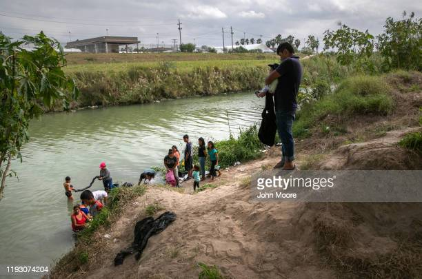 Asylum seekers wash clothes on the Mexican side of the Rio Grande at an immigrant camp on December 08 2019 in the border town of Matamoros Mexico...