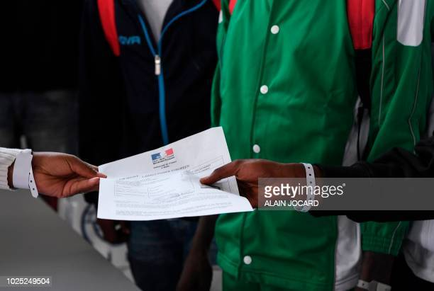 Asylum seekers who have been rescued by the Aquarius rescue ship and another ship in the Mediterranean sea hold an official document delivered by the...