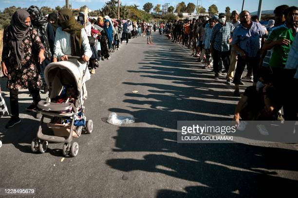 Asylum seekers, women on the one side and men on the other, queue for food distribution along the roadside where thousands are living with out...