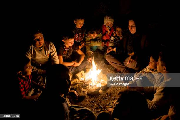 Asylumseekers gather around a fire to try to get warm after spending the day under a cold rain outside Moria Camp where they are meant to register...