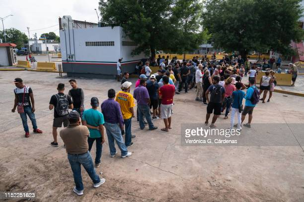 Asylumseekers wait in line to get a meal close to the International Bridge near a section where a father and daughter drowned attempting to cross...