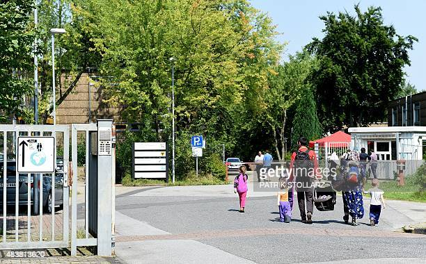 Asylumseekers walk in to a refugee reception facility in Dortmund Germany on August 13 2015 The overcrowded facility in Dortmund has seen the largest...