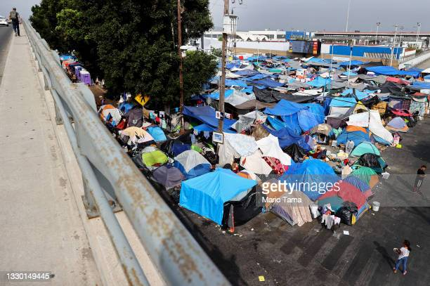 Asylum-seeking migrants gather at a makeshift camp on the Mexican side of the San Ysidro Port of Entry on July 22, 2021 in Tijuana, Mexico. Around...