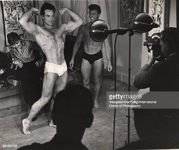 At a beauty contest for men, a muscular man wearing a bathing suit, flexes his muscles in the spotlight, while the judge, a French female artist,...