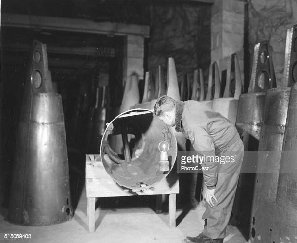 At a captured V1 Factory located in an old iron mine Mine de Thil 1st Lt Jack Ebinger inspects a V1 tail assembly that never was completed Thil...