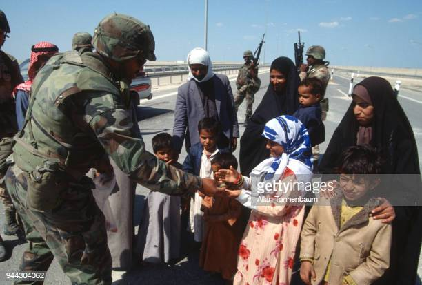 At a checkpoint American soldiers give candy to a group of children during the Gulf War Iraq 1991
