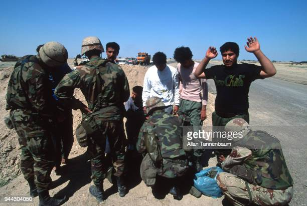 At a checkpoint American soldiers pat down a group of men by the side of the road during the Gulf War Iraq 1991