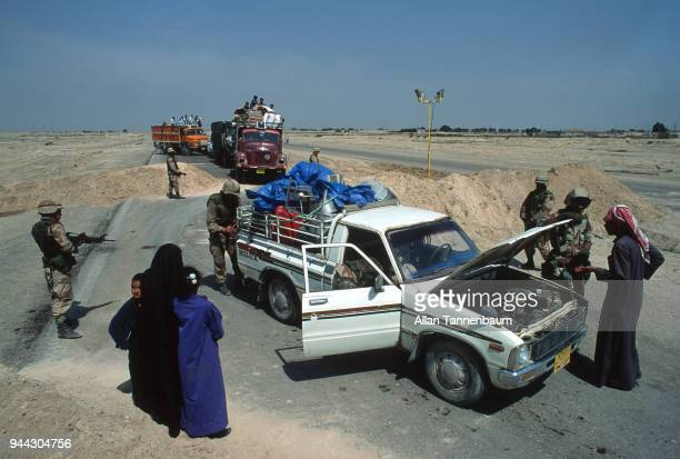 At a checkpoint during the Gulf War American soldiers examine an Iraqi family's pickup truck Iraq 1991