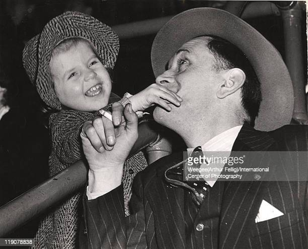 At a circus performance a young girl laughs as she covers the mouth of a man in a pinstripe suit New York New York April 6 1944 Photo by...