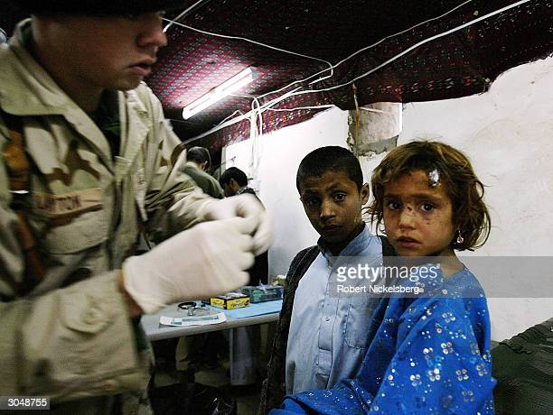 At a Coalition Forces military base, a U.S. Navy medic checks the infected head wound of an Afghan girl February 2, 2004 in Asadabad, the capital of...